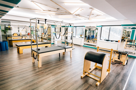 61304539 - room full of pilates equipment: exochairs, ladder barrel, reformer, cadillac and trapeze table