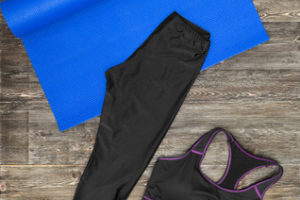 47665149 - woman's yoga outfit on wooden background
