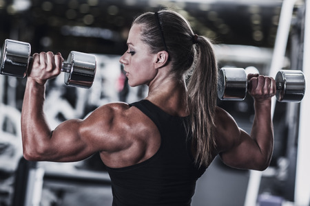 31336532 - young woman bodybuilder with dumbbells.