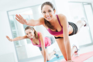 42511536 - sporty young women at the gym doing pilates workout on a mat, fitness and healthy lifestyle concept