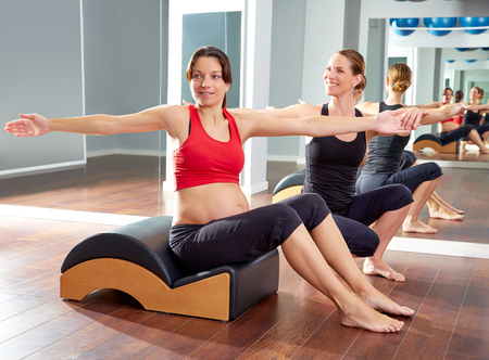 44274407 - pregnant woman pilates exercise spine twist with wave corrector and personal trainer
