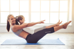 63888759 - beautiful young woman and charming little girl are smiling while doing yoga together in fitness hall